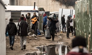 Migrants move their belongings through the camp known as the Jungle in Calais.