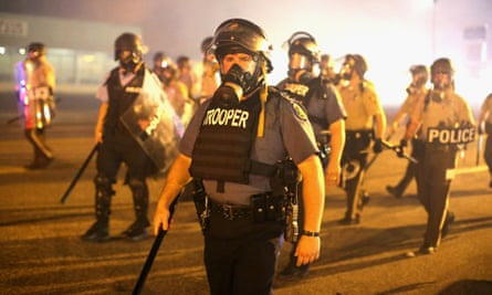 Police advance through a cloud of tear gas toward demonstrators protesting the killing of teenager Michael Brown in Ferguson.