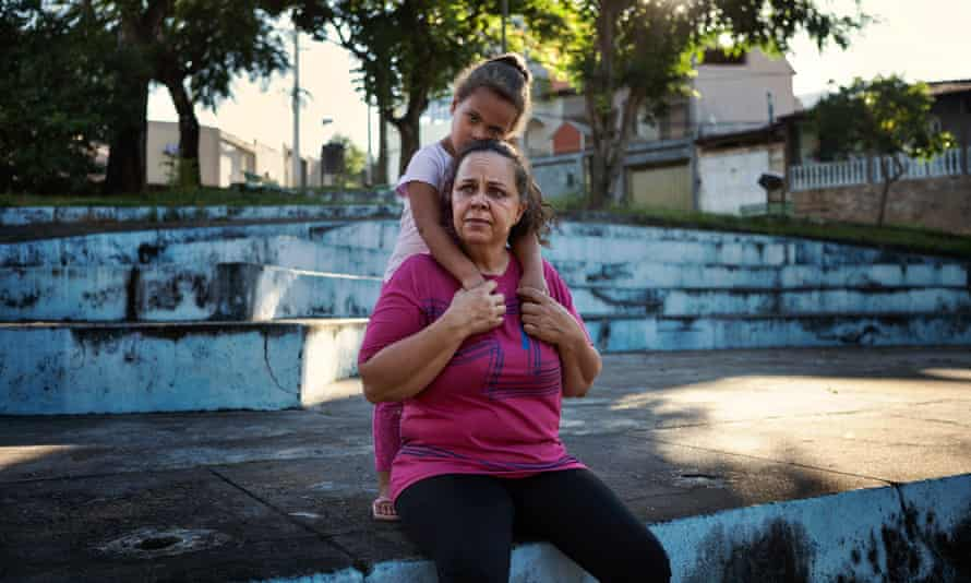 Sandra Quintão, a survivor from Bento Rodrigues, with her daughter in front of a temporary new house in Mariana.