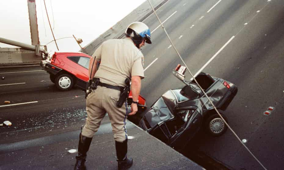 In a 17 October 1989 photo, a California highway patrol officer checks the damage to cars that fell when the upper deck of the Bay Bridge collapsed onto the lower deck after the Loma Prieta earthquake in San Francisco.