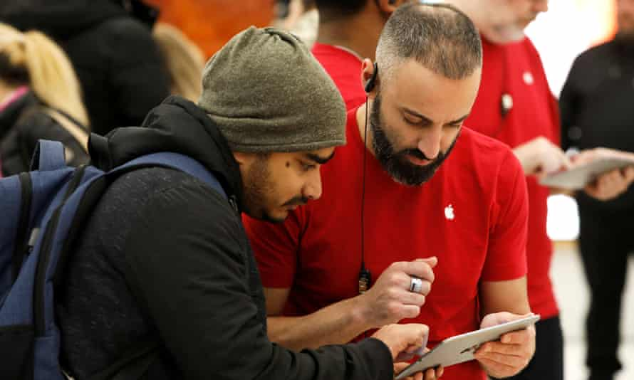 """At the World Trade Center Apple store, an in-house """"genius"""" helps a customer."""