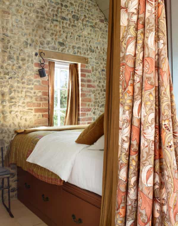 William Morris fabric divides the rooms and the bed with storage underneath.