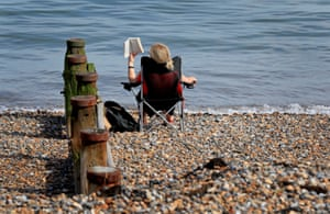 Herne Bay, England: A woman reads on the beach during the morning sunshine