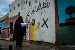A woman walks by an mural discouraging domestic violence outside if Al-Shifa hospital
