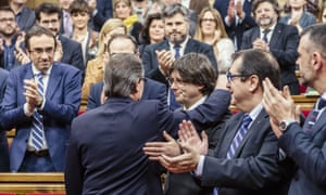 Carles Puigdemont is congratulated by the acting Catalan president, Artur Mas, front left, as he arrives for the investiture debate.