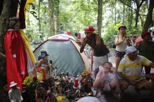 Followers of indigenous goddess Maria Lionza smoke cigars during purification rituals and to deflect evil spirits, next to an altar featuring her statue on Sorte Mountain, where followers of the goddess gather annually in Venezuela's Yaracuy state. Many camped in tents among the old-growth forest while dedicating several days to spiritual ceremonies