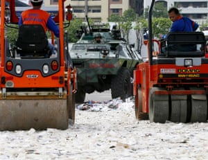 An armoured personnel carrier and road rollers crush fake DVDs and sunglasses in Quezon City, Philippines