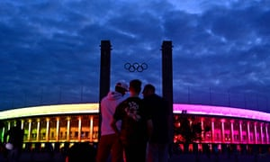 People stand in front of Berlin's Olympic stadium as it is illuminated with the Rainbow colours