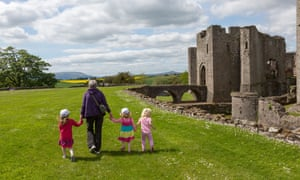 Woman and children walking alongside ruined castle at Raglan