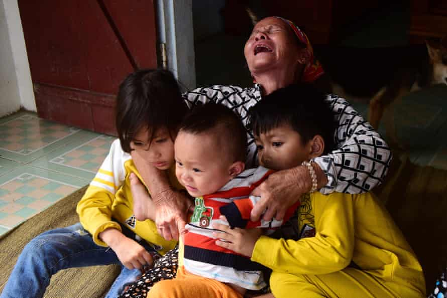 Cao Thi Uyen, mother of Cao Huy Thanh, holds her grandson, centre, at her home in Nghe An province in Vietnam.