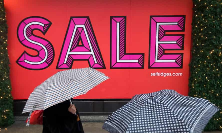 Shoppers visiting the Boxing Day sales during wet and rainy weather in Oxford Street