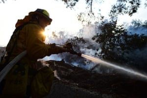A firefighter controls flames at a home set ablaze by the Skirball fire in Bel-Air.