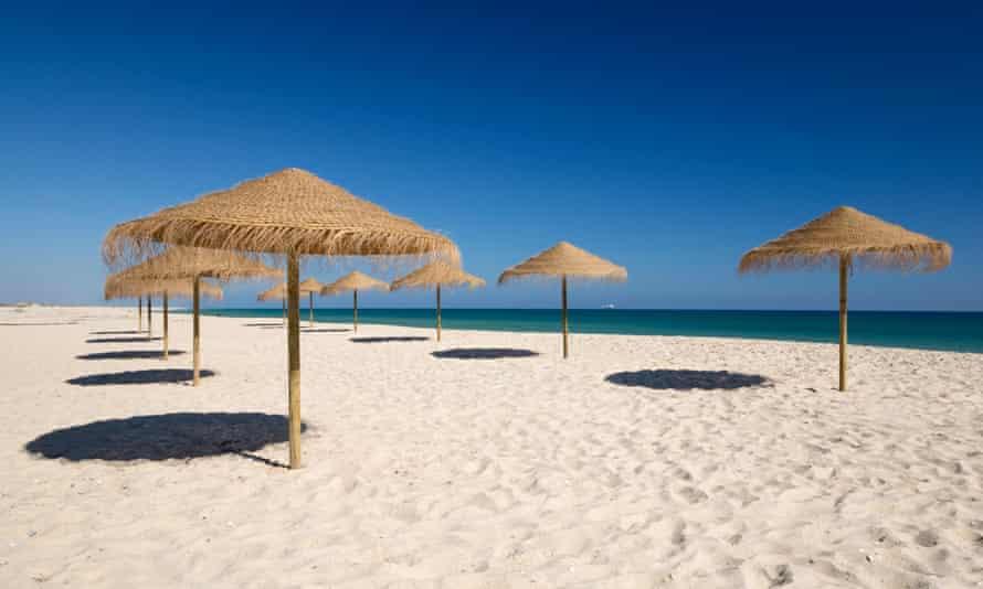 An empty beach on the Algarve, PortugalHKH903 Straw umbrellas on empty white sand beach with clear sea behind, Ilha do Farol, Culatra barrier island, Olhao, Algarve, Portugal