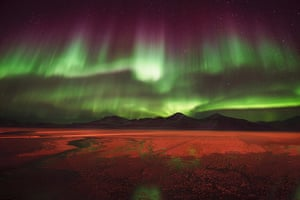 Aurora over SveaAgurtxane Concellon (Spain). The purples and greens of the Northern Lights radiate over the coal mining city of Svea, in the archipelago of Svalbard. The earthy landscape below the glittering sky is illuminated by the strong lights of industry at the pier of Svea
