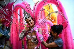 A dancer looks on as she is dressed to perform.