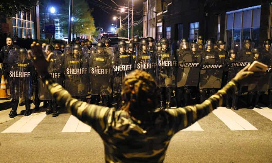A protester faces police in riot gear as they force people off a street in Elizabeth City, North Carolina.