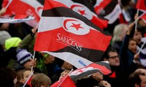 Saracens fans wave flags at a match