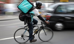 A Deliveroo rider cycles through central London