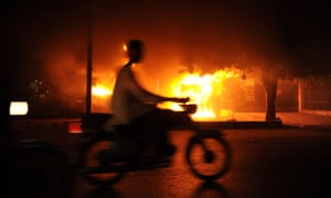 A Pakistani man rides past by burning shop set alight by protesters in Karachi on August 2, 2010
