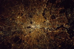 London at nightThe River Thames flows through the centre, with many of London's famous bridges visible. The distinctive Isle of Dogs and Thames Barrier can also be seen. The central dark regions mark London's royal parks, with Richmond Park lower left.