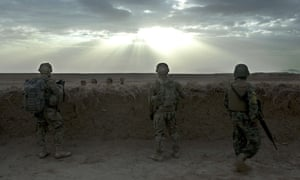 Two US soldiers with an Afghan colleague (right) secure a position behind a mud wall in Daman district, Kandahar, Afghanistan