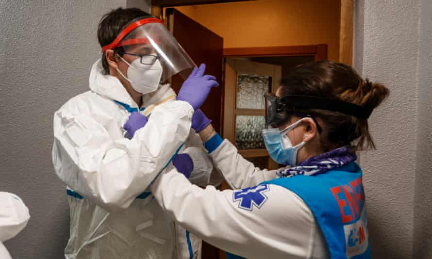 Marta helps Dr Mateo into his protective uniform. Before entering the house to attend an emergency, the security protocol indicates that medical staff must put on the isolation suits.