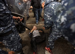 Beirut, Lebanon: Policemen surround an anti-government protester