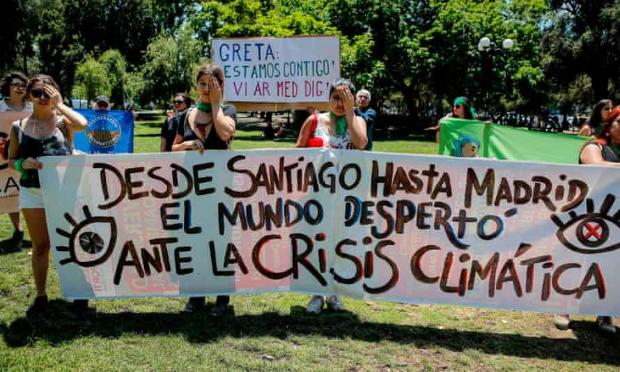 Environmental protesters in Santiago, Chile. Their banner reads: 'From Santiago to Madrid, the world has woken up to the climate crisis.'