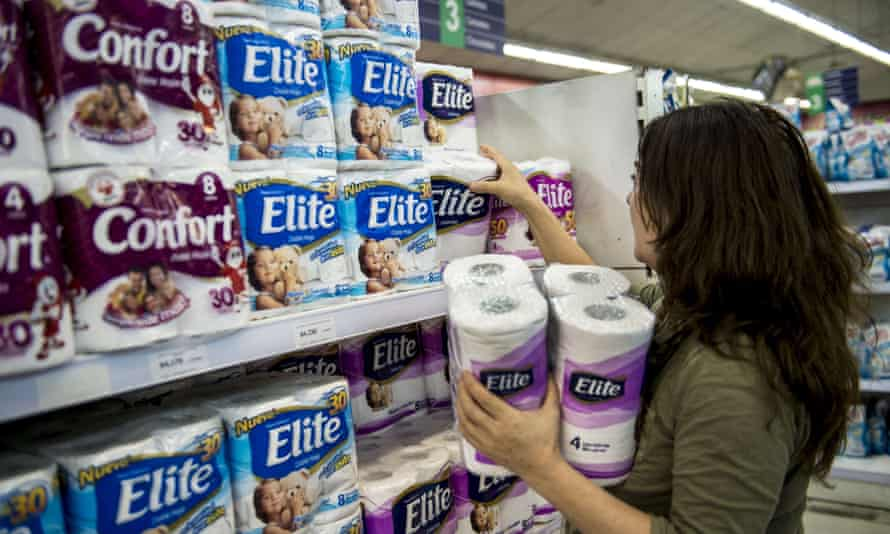 A woman buys toilet paper at a supermarket in Chile, where a price-fixing cartel has been exposed.