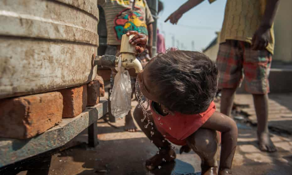 A boy drinks from the tap of a water tank outside a night shelter in New Delhi, India.