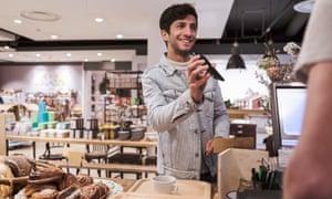Cliente masculino que mostra o telefone celular ao fazer o pagamento sem contato ao caixa no café
