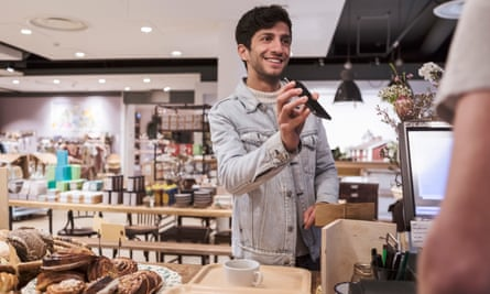 Male customer showing mobile phone while doing contactless payment to cashier at cafe