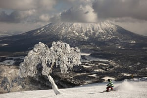 A man snowboards down a slope at a ski resort overlooking Mount Yotei.