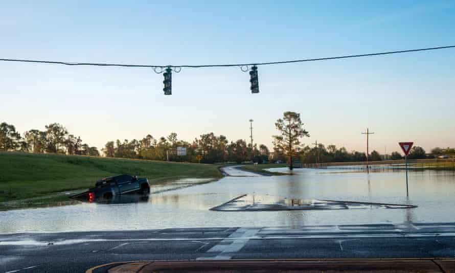 A submerged car is pictured on a flooded street after Hurricane Delta in October last year. 'Climate change is something that is affecting this community,' said the city's Republican mayor.