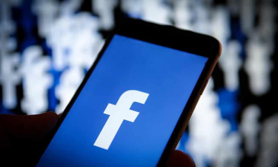 A Facebook logo is seen on an iPhone screen.