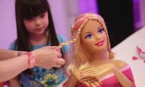 A five-year-old girl watching while a Barbie doll has her hair plaited