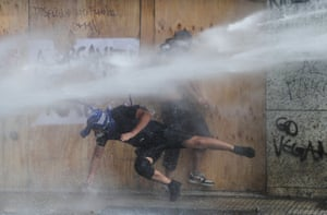 Demonstrators are sprayed by security forces with water cannon