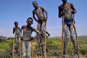 Young boys from the Mursi tribe walk on stilts