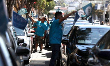 Rideshare drivers wave flags during a rally in San Francisco.