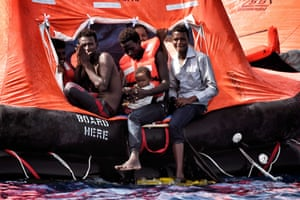 Migrants wait to be rescued with a baby in their arms