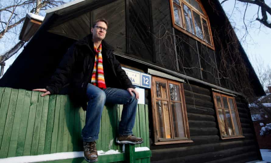 Luke Harding in a colourful scarf sitting on a fence by a wooden house