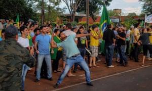 An opponent of the former Brazilian president Luiz Inácio Lula da Silva throws stones during a demonstration.