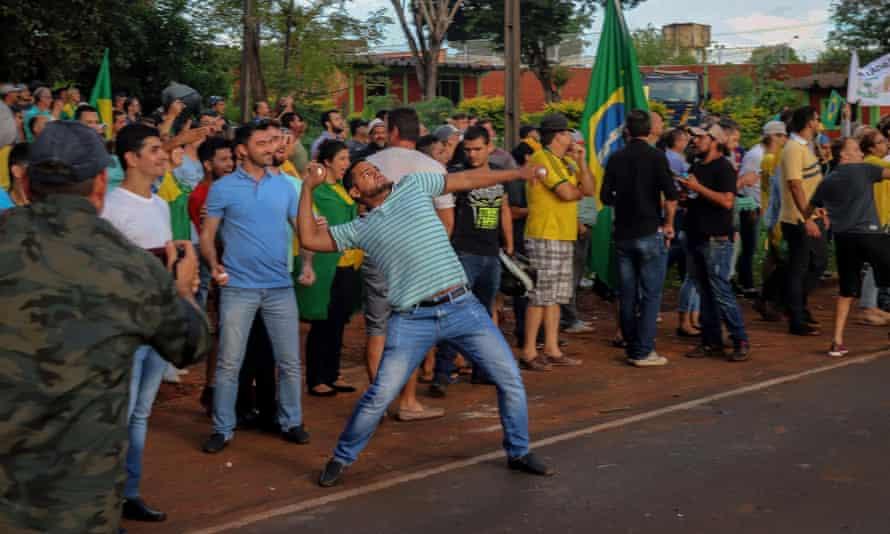 An opponent of former Brazilian president Luiz Inacio Lula da Silva throws stones during a demonstration.