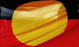 A woman is silhouetted behind the Aboriginal flag