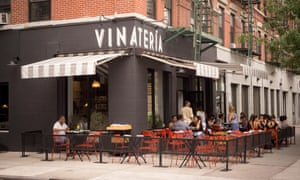 Patrons sit at the outdoor cafe of the Vinateria restaurant on Frederick Douglass Blvd in the neighborhood of Harlem in New York, US.