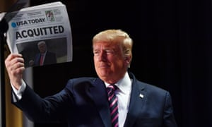 Donald Trump holds up a newspaper that displays the headline 'Acquitted'