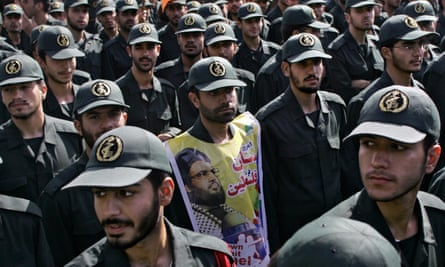 Members of the Iranian Revolutionary Guards, one of them covering his chest with a portrait of Lebanon's Hezbollah leader Hassan Nasrallah.