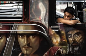 Custom artwork on the side of a jeepney as a driver's assistant waits for passengers.