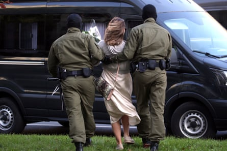 Masked law enforcement officers detain a woman during a protest on Saturday