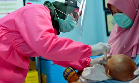 A medic in Banda Aceh, Indonesia, gives polio and rubella vaccines to a baby in May 2020.